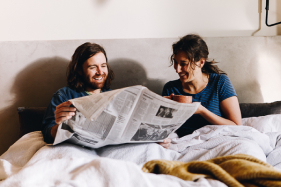 couple             reading the newspaper and drinking coffee in bed after waking up             refreshed