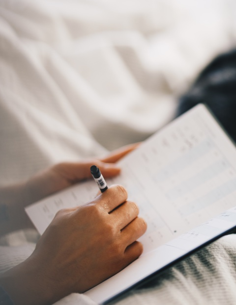 Woman filling out her Kick sleep journal in bed right after             waking up