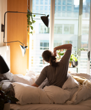 woman stretching             in bed while looking out the window at the morning sun
